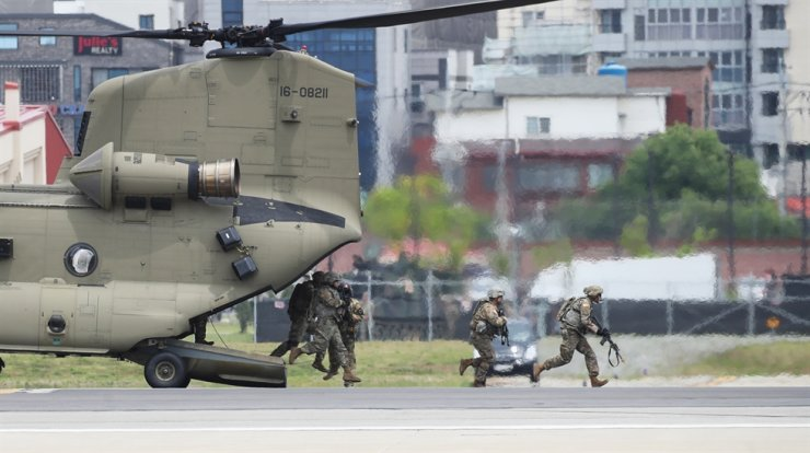 Soldiers of the U.S. Eighth Army, which is stationed at the U.S. Forces Korea (USKF) Camp Humphreys base in Pyeongtaek, Gyeonggi Province, exit a helicopter during a combat training demonstration in this June 2019 photo. / Yonhap