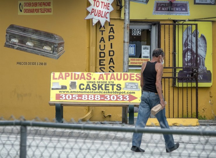 A man walks in front of a casket advertising in near to the entrance of the 'Monument and Casket Depot' in Hialeah, Florida, USA, 22 September 2020. EPA-Yonhap