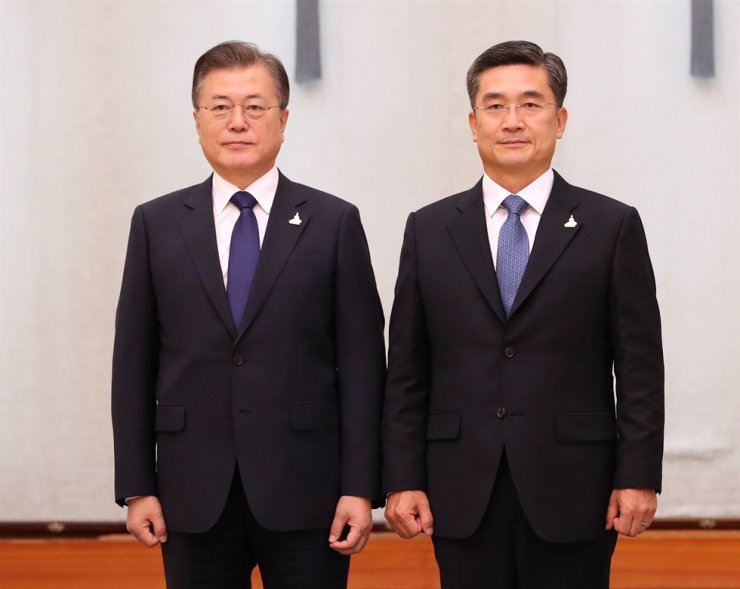 Defense Minister Suh Wook, right, poses with South Korean President Moon Jae-in for photo after being appointed to the ministerial position at Cheong Wa Dae, Sept. 18. Korea Times file