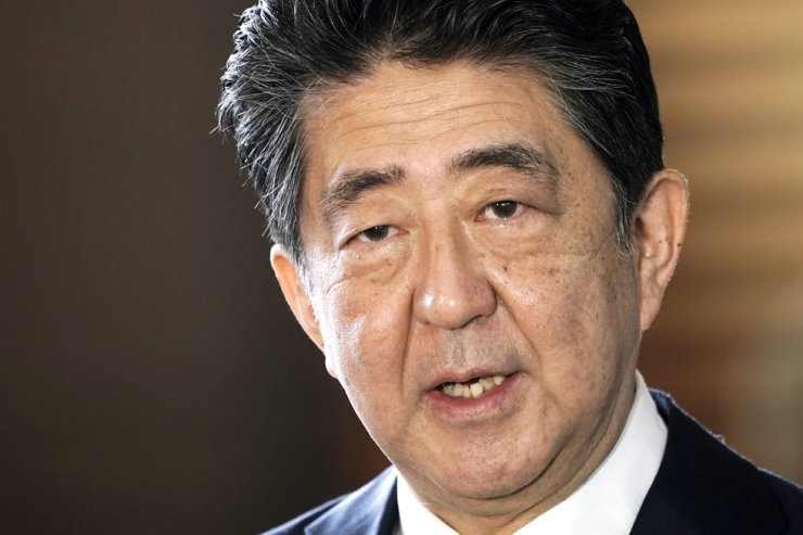 Japan's outgoing Prime Minister Shinzo Abe speaks to the media as he arrives at the prime minister's office for a Cabinet meeting in Tokyo, in this Sept. 16, file photo. Abe tweeted Saturday that he had visited a shrine viewed by China and both Koreas as a symbol of wartime aggression. AP