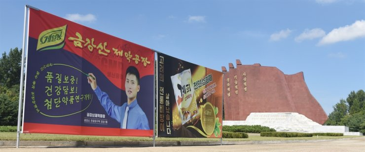 Billboards for North Korean companies stand next to a monument to the Three Revolutions. / Korea Times photo by Jon Dunbar