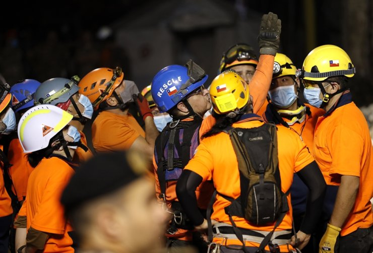 The leader of the Chilean rescuers, center, gives his team direction in where to start searching the site of a collapsed building after getting signals there may be a survivor under the rubble, in Beirut, Lebanon, early Friday, Sept. 4, 2020. AP-Yonhap