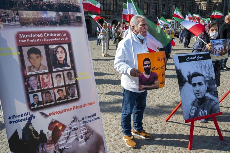 A man holds a portrait of Iranian wrestler Navid Afkari during a demonstration on the Dam Square in Amsterdam, the Netherlands, on Sunday, against its execution in the southern Iranian city of Shiraz and against the Iranian government. AFP-Yonhap