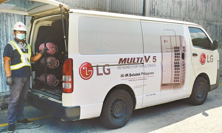 An LG Electronics employee stands next to a van for LG's Direct Mobile Service (DMS), a mobile air-conditioning service, Sunday. The DMS business has been expanded to three additional countries ― the Philippines, Indonesia and Australia ― providing its service to six countries in total. / Courtesy of LG Electronics