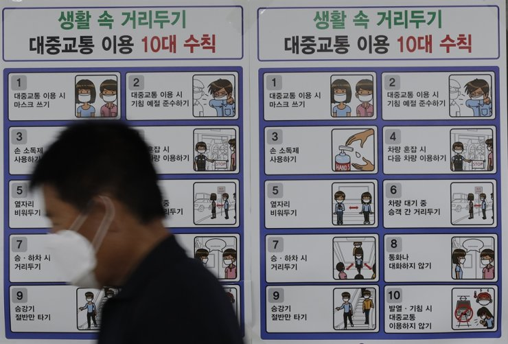 A man wearing a face mask walks past a banner showing precautions against the coronavirus at subway station in Seoul, Thursday, Sept. 10, 2020. AP