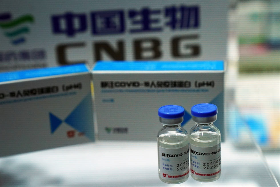 An employee answers questions from the public near samples of a COVID-19 vaccine produced by Sinopharm subsidiary CNBG that are displayed during a trade fair in Beijing on Sunday, Sept. 6, 2020. AP-Yonhap