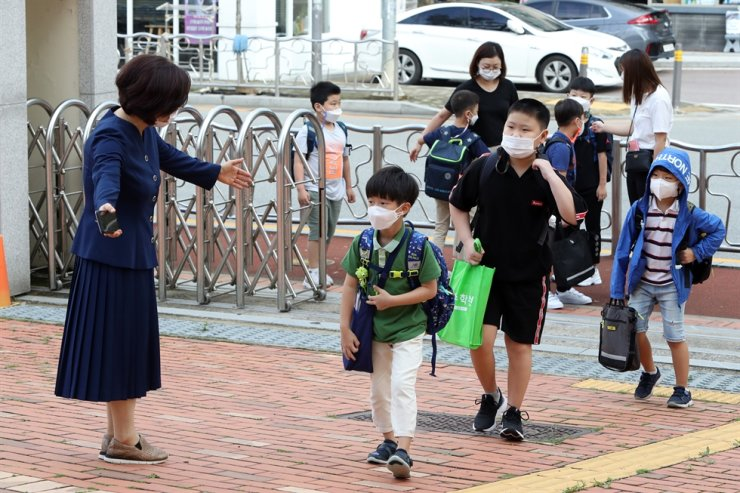 A teacher greets students at an elementary school in the southwestern city of Gwangju after the school reopened Monday. It had previously implemented online classes amid fears over the spread of COVID-19. / Yonhap
