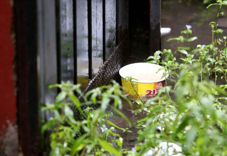 An instant noodle bowl is seen near the home of two boys who were seriously injured by a fire while cooking in Incheon, Sept. 17. Yonhap