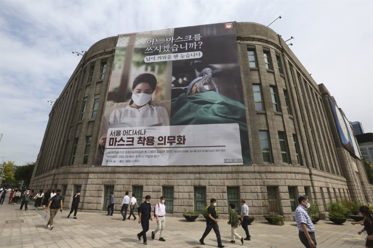 People wearing face masks to help protect against the spread of the coronavirus walk under a banner informing mandatory mask wearing in front of Seoul City Hall in Seoul, Thursday, Sept. 17, 2020. AP