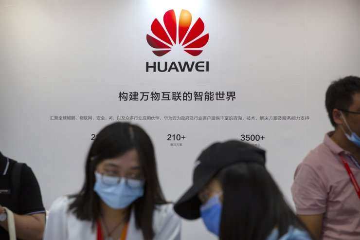 Visitors wearing face masks to protect against the coronavirus stand at a booth for Chinese technology firm Huawei at the China International Fair for Trade in Services in Beijing, Saturday, Sept. 5, 2020. AP