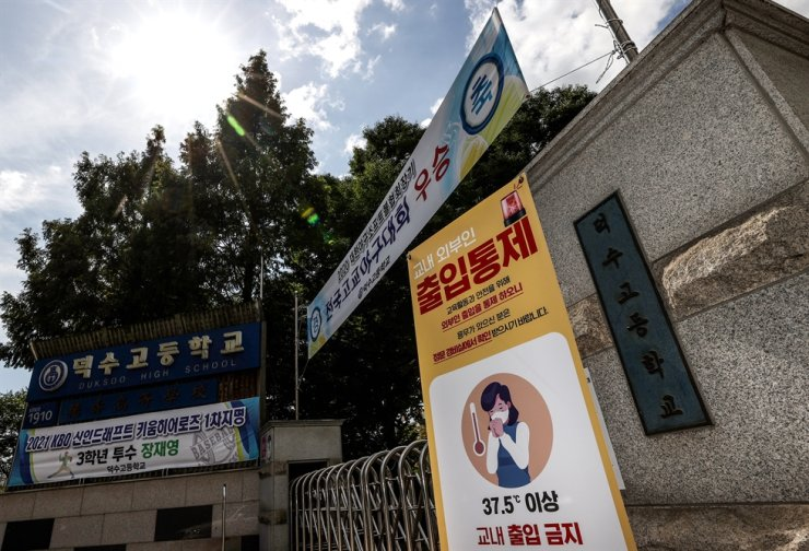 Duksoo High School in Seoul's Seongdong-gu District on Sept. 26 displays a poster informing outsider visitors not to enter with its main entrance gate shut. From Sept. 24, three of the school's baseball team members were infected with COVID-19. Yonhap