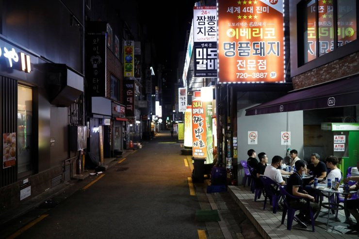 People drink outside as tougher social distancing rules that have been announced on the last Friday continue, in Seoul, Aug. 31, 2020. Reuters