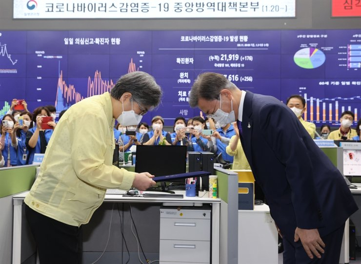 President Moon Jae-in and Jeong Eun-kyeong, the first head of the Korea Disease Control and Prevention Agency (KDCA), bow to each other after the former presented the latter with a certificate of appointment during a ceremony at the emergency situation room of the agency in Cheongju, North Chungcheong Province, Friday. The Korea Centers for Disease Control and Prevention (KCDC) has been upgraded to the KDCA and Jeong, who was the chief of the KCDC, was appointed to lead the new body. Yonhap