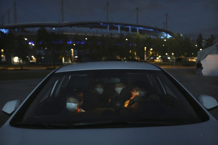 Family members in a car watch a drive-in circus from a parking lot in Seoul, Friday, Sept. 25, 2020. AP