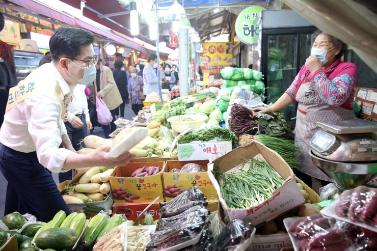 Seoul Gangdong-gu District Mayor Lee Jung-hun, left, meets one of the merchants at Dunchon-dong Subway Station street market in the district's Dunchon-dong area on Sept. 22. Yonhap