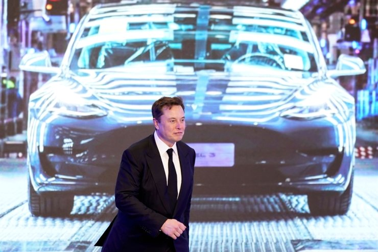 Tesla CEO Elon Musk walks next to a screen showing an image of a Tesla Model 3 car during the opening ceremony for Tesla's China-made Model Y program in Shanghai, Jan. 7. Reuters-Yonhap