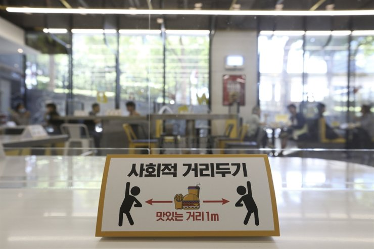 A social distancing sign is seen on a table to help curb the spread of the coronavirus at No Brand Burger in Seoul, Sunday, Sept. 13, 2020. AP