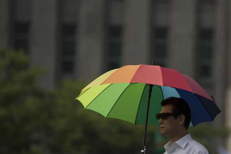 A man holds a rainbow umbrella during the 2015 Queer Festival in Seoul. / Korea Times photo by Choi Won-suk
