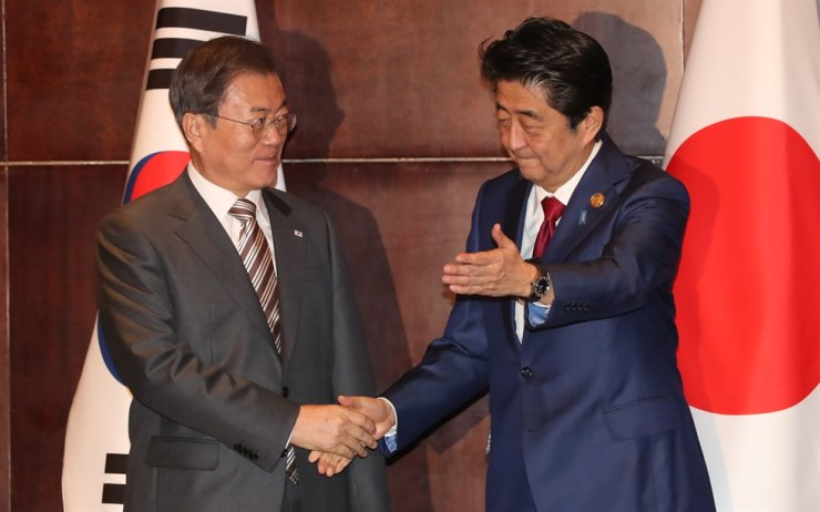 President Moon Jae-in, left, shakes hands with Japanese Prime Minister Shinzo Abe ahead of a summit in Chengdu, China, on Dec. 24, 2019. Korea Times file