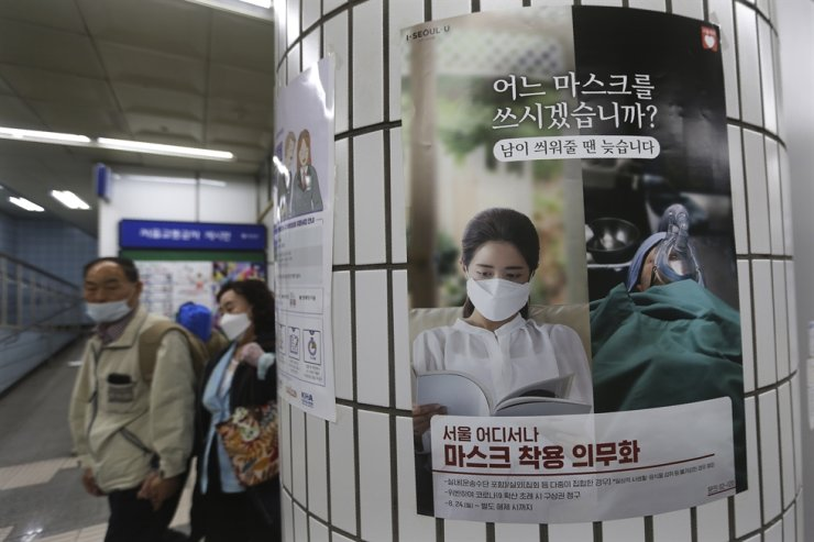 People wearing face masks to help protect against the spread of the coronavirus walk by a poster informing mandatory mask wearing at a subway station in Seoul, Sunday, Sept. 20, 2020. AP