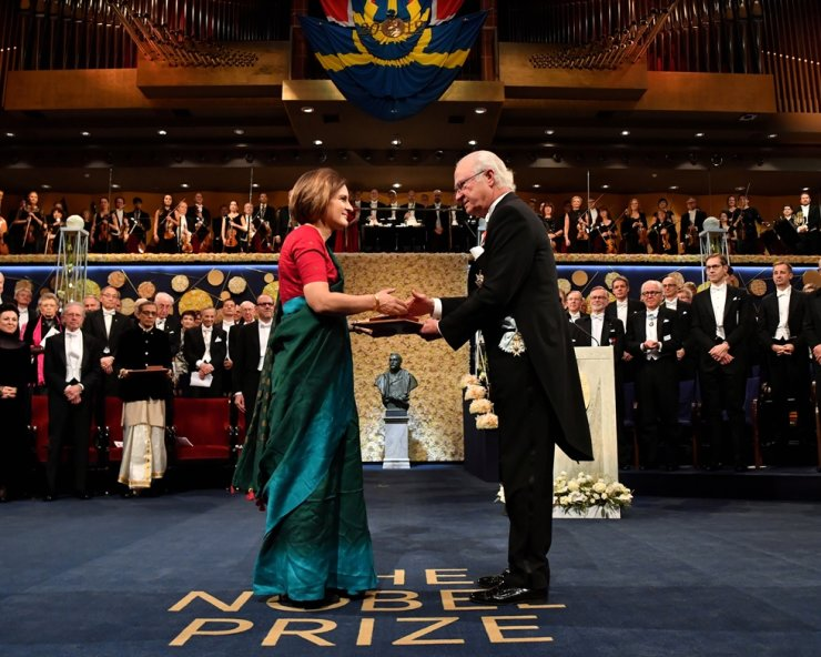 French economist Esther Duflo shakes hands with Sweden's King Carl Gustaf as she receives the Sveriges Riksbank Prize in Economic Sciences in Memory of Alfred Nobel during the Nobel Prize award ceremony at the Stockholm Concert Hall in Stockholm, Sweden December 10, 2019. REUTERS-Yonhap