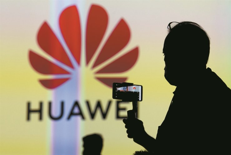 A silhouette of a visitor next to the logo of Huawei is displayed on a screen at the Huawei stand at the IFA fair in Berlin, Sept. 3. EPA-Yonhap