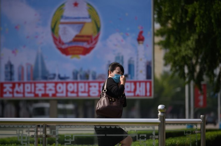 A woman wearing a face mask exits an underpass before a poster commemorating the 72nd anniversary of the founding of North Korea, in Pyongyang, Sept. 9, 2020. AFP