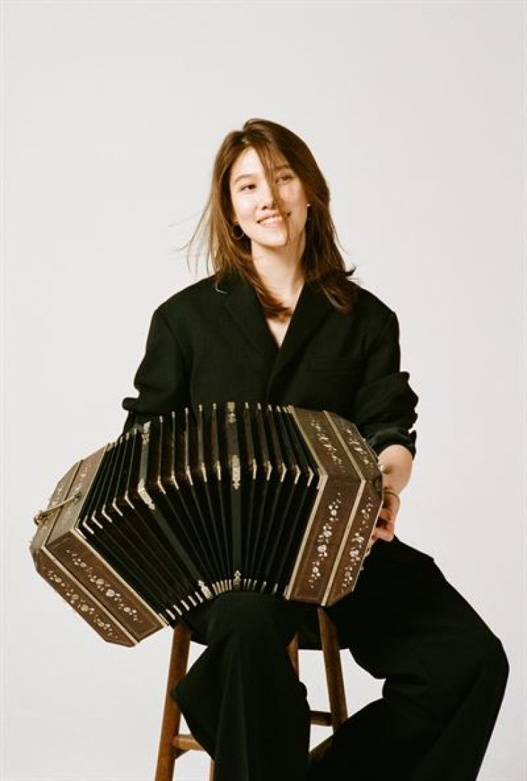 Koh Sang-ji, one of Korea's first bandoneonists, poses with the Argentinean folk instrument. Her latest activity includes joining the Stay Joyful online concert hosted by the Korea Foundation to overcome COVID-19 and promote cultural exchanges with other countries. / Courtesy of Private Curve