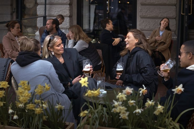 In this Wednesday, April 8, 2020, file photo people chat and drink outside a bar in Stockholm. Sweden's relatively low-key approach to coronavirus lockdowns captured the world's attention when the pandemic first hit Europe. But it also had a per capita death rate much higher than other Nordic countries. Now, as infection numbers surge in much of Europe, Sweden has some of the lowest numbers of new cases and there are only 14 people being treated for the virus in intensive care in the country of 10 million. AP