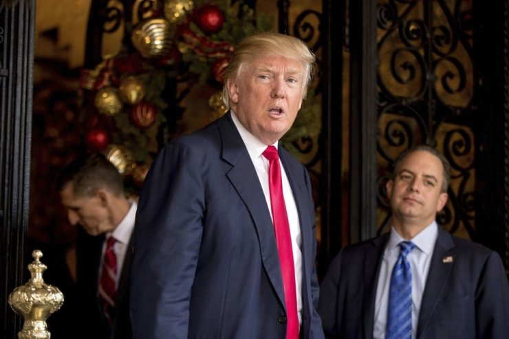 In this Dec. 21, 2016, file photo, U.S. President-elect Donald Trump, accompanied by chief of staff Reince Priebus, right, and retired Gen. Michael Flynn, a senior adviser to Trump, stand together at Mar-a-Lago, in Palm Beach, Fla. AP