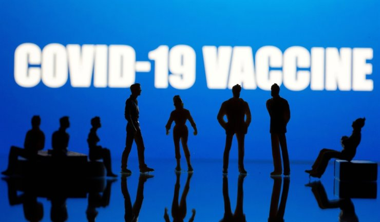 Small toy figures are seen in front of a 'COVID-19 Vaccine' logo in this illustration taken, Sept. 9, 2020. Reuters