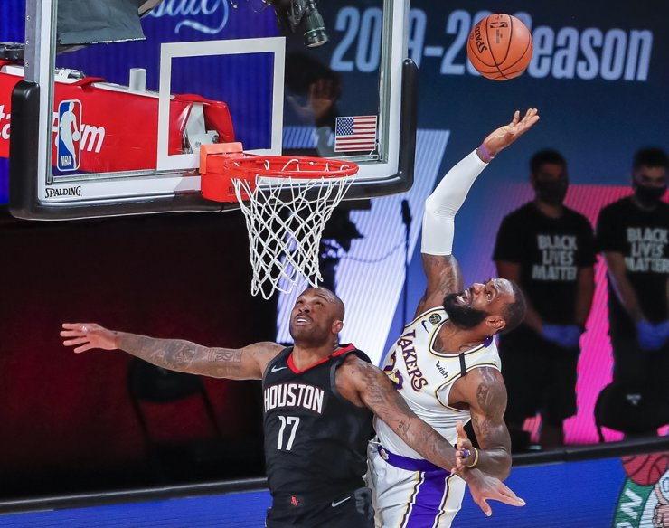 Los Angeles Lakers forward LeBron James, right, is fouled by Houston Rockets forward P.J. Tucker during the second half of the NBA basketball semi final Western Conference playoff game three between the Los Angeles Lakers and the Houston Rockets at the ESPN Wide World of Sports Complex in Kissimmee, Fla., Tuesday. / EPA-Yonhap