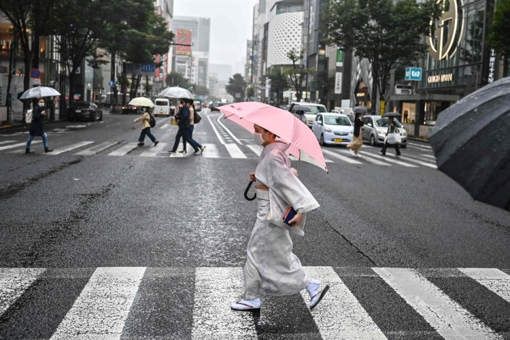 A woman wearing traditional dress uses an umbrella to shelter from the rain while crossing a street in Tokyo on Sept. 24, 2020. Thomas Bach, chief of the International Olympic Committee, said the Tokyo Games could take place next year even without a coronavirus vaccine. AFP
