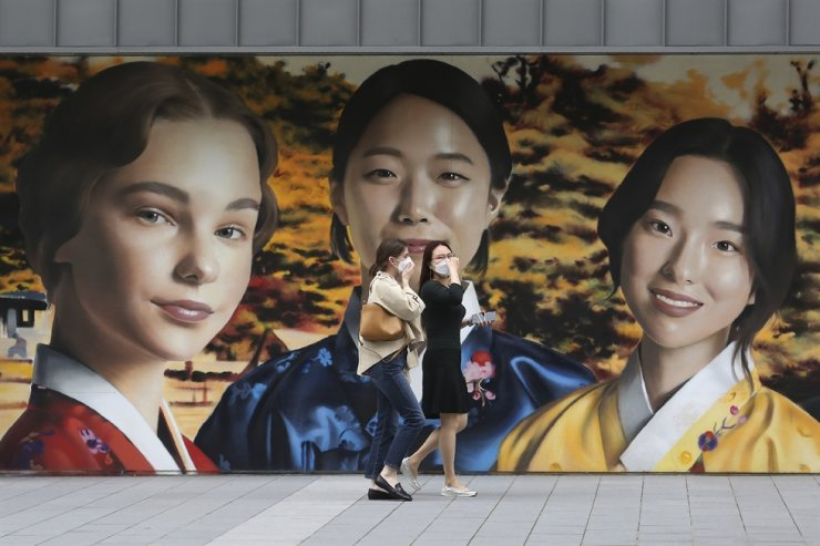 Women wearing face masks to help protect against the spread of the coronavirus pass by a street art wall in front of the Korea Tourism Organization in Seoul, Thursday, Sept. 17, 2020. AP