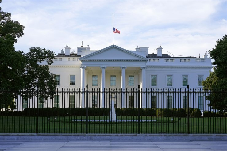 In this Saturday, Sept. 19, 2020, file photo, an American flag flies at half-staff over the White House in Washington. A woman suspected of sending an envelope containing the poison ricin, which was addressed to White House, has been arrested at the New York-Canada border. AP