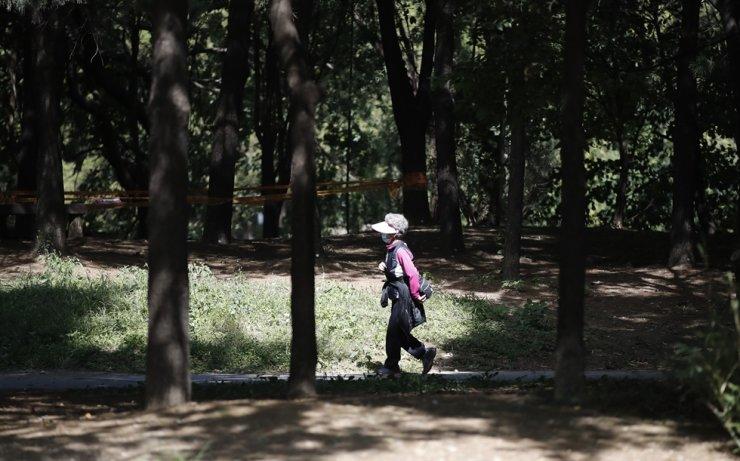 A woman wearing a face mask as a precaution against the coronavirus walks at a park in Seoul, Thursday, Sept. 24, 2020. AP