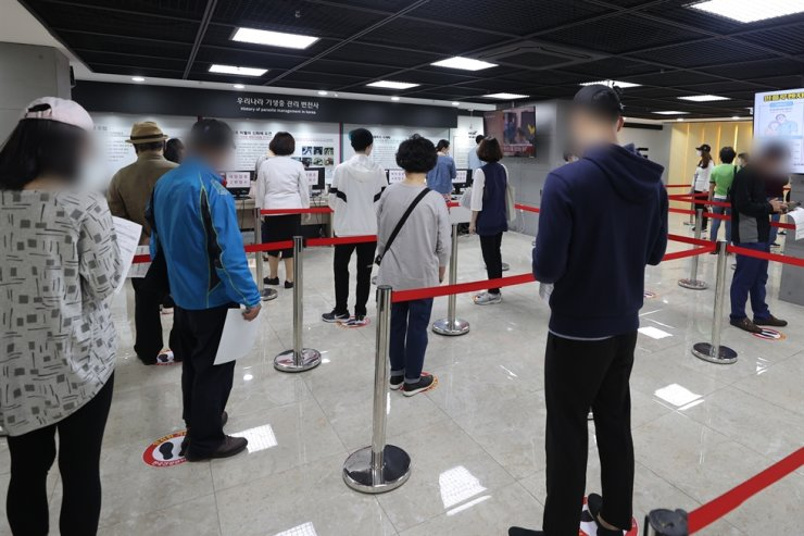 Citizens wait in long lines to get free flu vaccinations at the Korea Association of Health Promotion's Seoul branch, Thursday, as some vaccine bottles to be used for the government's free flu shot program were found to have been mishandled. / Yonhap