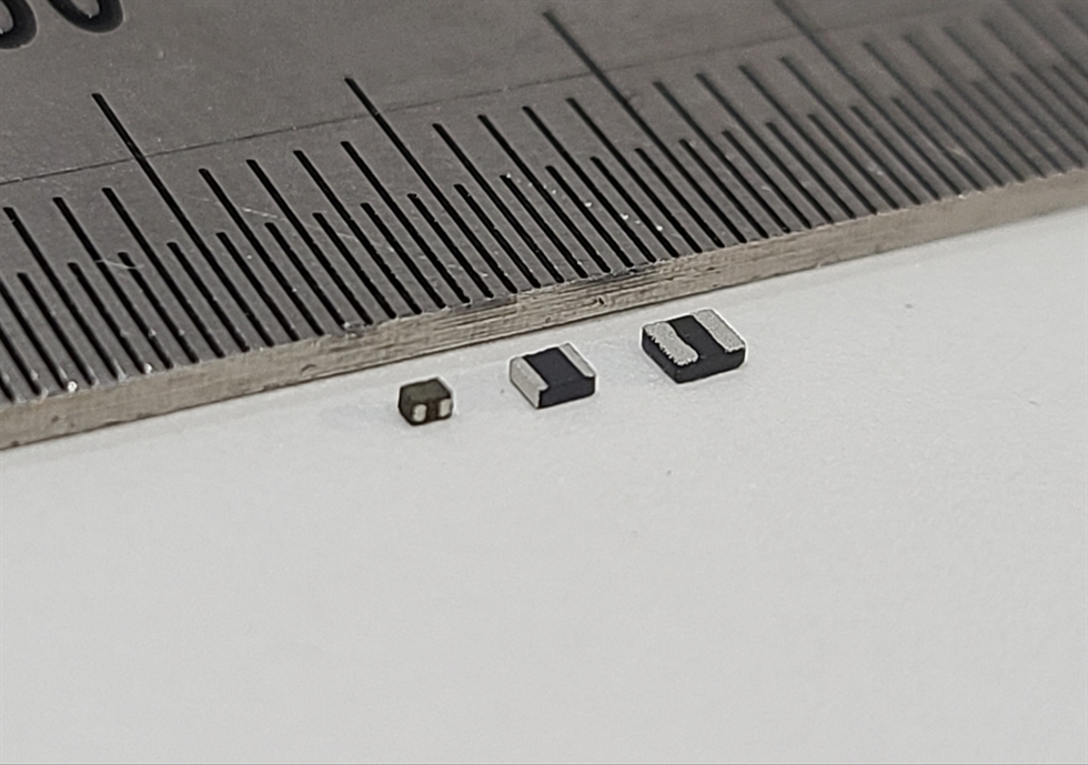Seen next to a smartphone are Samsung Electro-Mechanics' power inductors. The company said Sunday it successfully developed the industry's smallest power inductor, a core electronic component for electronic devices. / Courtesy of Samsung Electro-Mechanics