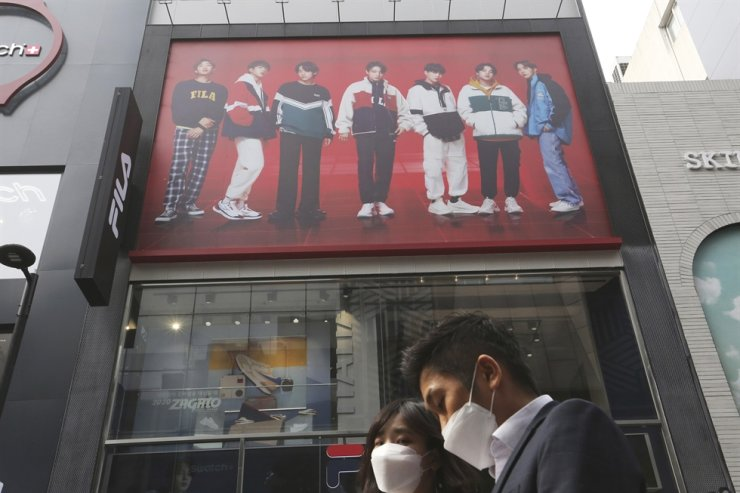 People walk past a commercial poster showing K-Pop group BTS at a shopping street in Seoul, Oct. 14, 2020. AP