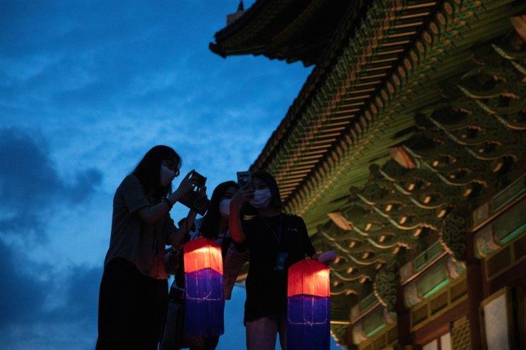 In this Aug. 14, 2020, file photo, women take selfies during a Changdeok Palace tour at night. Korea Times photo by Choi Won-suk