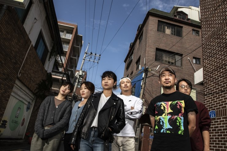 Members of 'Coreyah,' a gugak (traditional Korean music) crossover band, pose near their office in Mapo-gu, Seoul, Wednesday. From left are geomungo player Na Sun-jin, percussionist Kim Cho-rong, vocalist Ham Bo-young, guitarist Ko Jae-hyeon, wind instrument player Kim Dong-kun and percussionist Kyungyi. Korea Times photo by Choi Won-suk