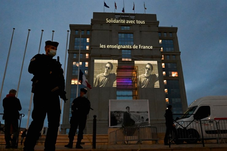 A portrait of French teacher Samuel Paty is projected along with cartoons of French satirical weekly newspaper Charlie Hebdo onto the facade of the Hotel de Region in Montpellier, on Oct. 21, 2020, during a national homage to French teacher Samuel Paty who was beheaded for showing cartoons of the Prophet Mohamed in his civics class. AFP