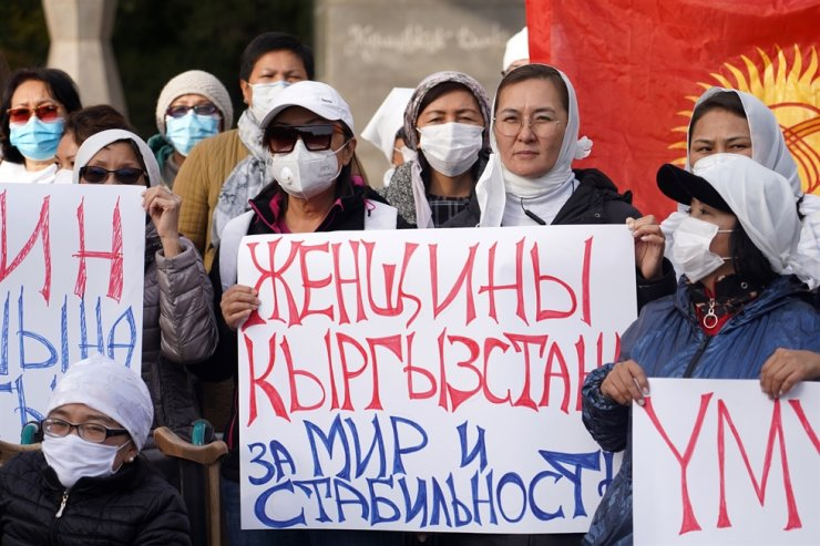 A woman carries a placard reading 'Women of Kyrgyzstan for Peace and Stability' during the White Headscarf march in support of social and political stability and in memory of Altynbek uulu Umutbek, 19, who died on October 5 amid mass unrest over the results of the parliamentary election. / Tass-Yonhap
