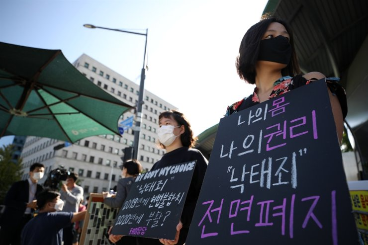 Activists gather in front of the National Assembly in Seoul, Wednesday, to demand lawmakers 'completely abolish' the law banning abortion. Yonhap
