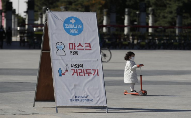 A banner showing mandatory mask wearing and social distancing as a precaution against the coronavirus, is seen at a park in Seoul, Saturday, Oct. 24, 2020. AP