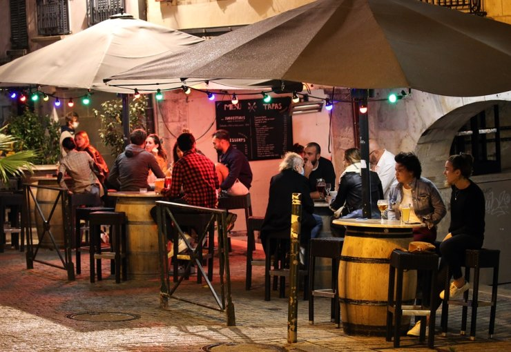 People drink in a bar terrace before the start of a new coronavirus curfew, in Bayonne, southwestern France, Thursday, Oct. 22, 2020. AP-Yonhap
