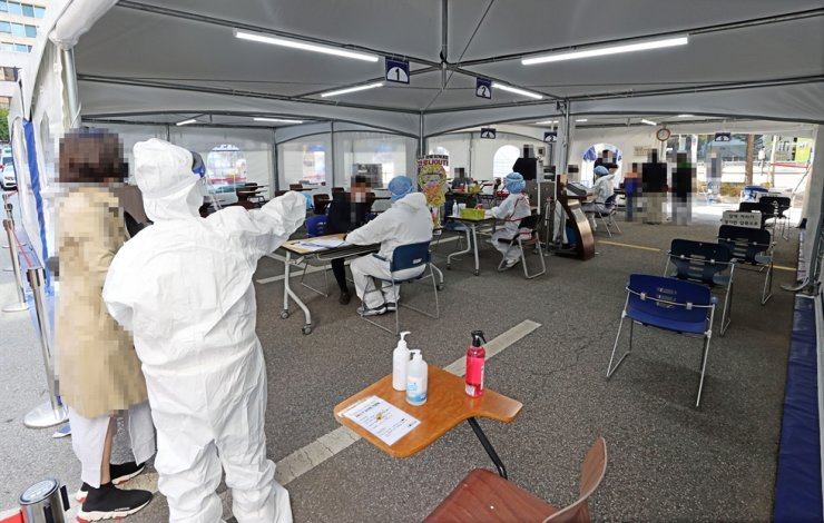 Residents in Seoul's Gangnam District go through COVID-19 testing at a public health center, Thursday, as a sauna in the area has reported at least 17 virus patients. / Yonhap