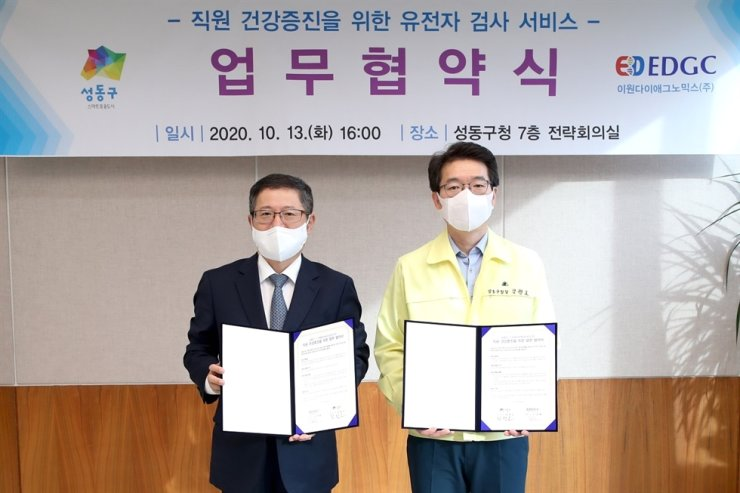 EDGC's co-CEO Shin Sang-cheol, left, and Seongdong District Office head Chong Won-o at the district office's headquarters on Oct. 13. EDGC will provide the district's employees and their families with home healthcare services that use the company's liquid biopsy-based predictive diagnosis. Courtesy of EDGC