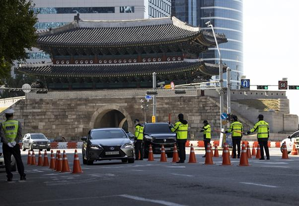 Cars drive past police buses that are parked surrounding the Gwanghwamun Square to prevent anti-government protests amid the COVID-19 pandemic in central Seoul, Friday. Yonhap