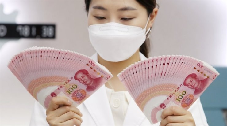 An official from Hana Bank's counterfeit analysis center takes a look at Chinese yuan notes at its office in Seoul, May 26. Yonhap